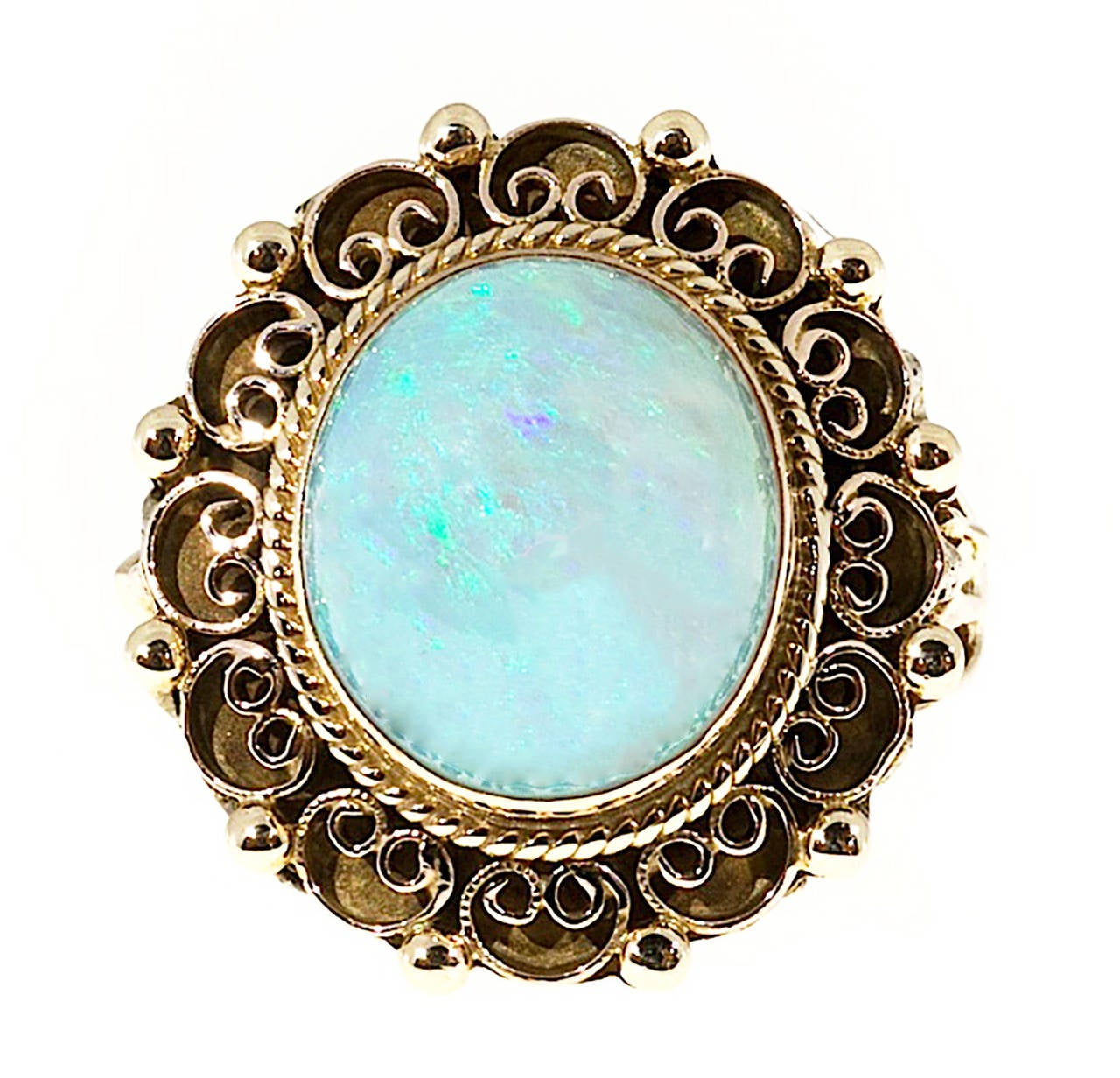 Open work scroll design 14k yellow gold ring with a well-polished natural Opal. High dome and very bright. Circa 1940.  1 oval natural bluish green Opal, approx. total weight 3.50cts, 12.5 x 11mm, orange flash 14k Yellow Gold Tested and stamped: