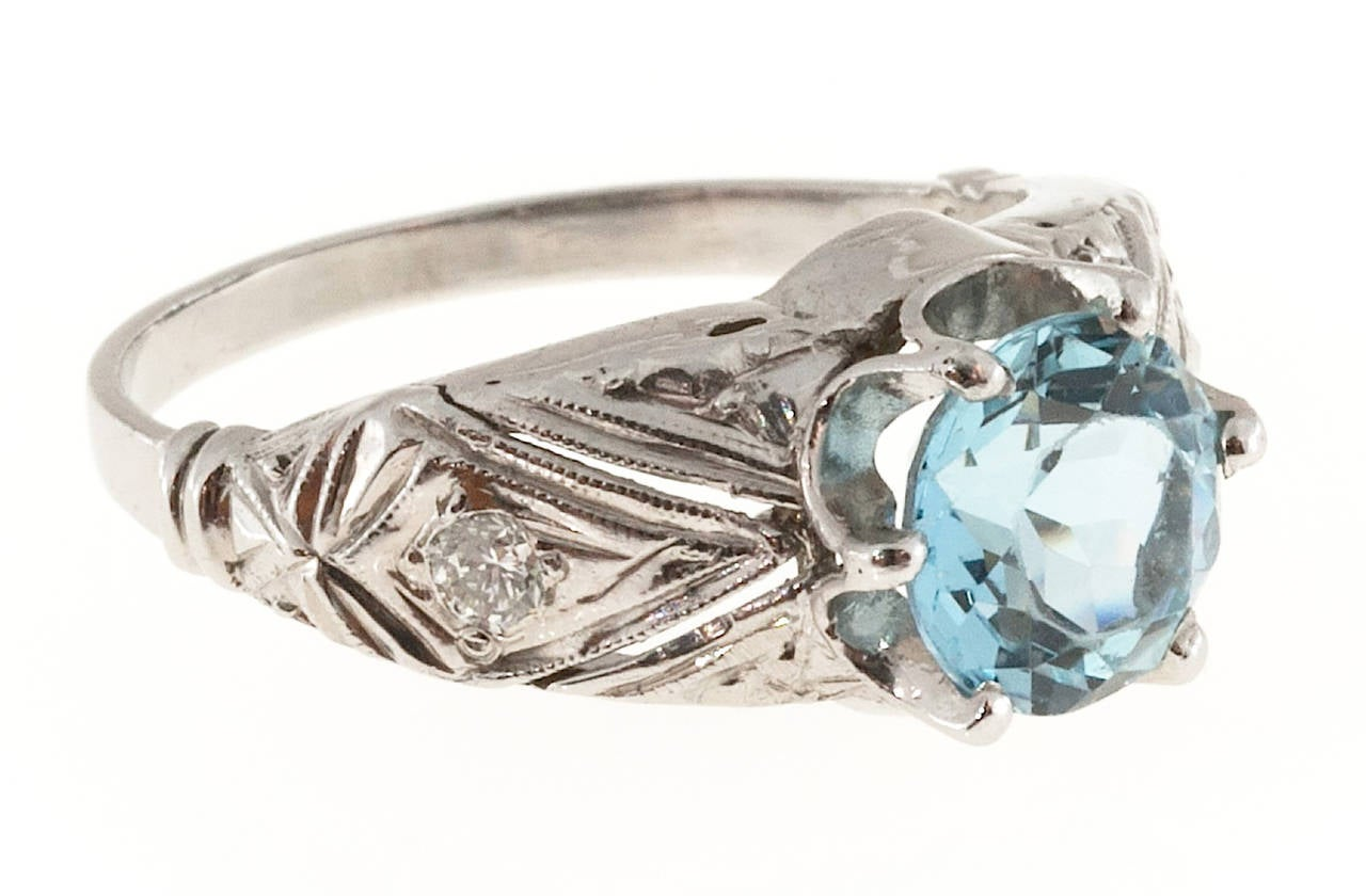 Engraved and filigreed ring with a beautiful natural gem untreated aquamarine center stone and a hand pierced and detailed ring.   1 6.85mm top gem European cut bright blue Aqua, approx. total weight 1.50cts, VS, natural color and untreated  2