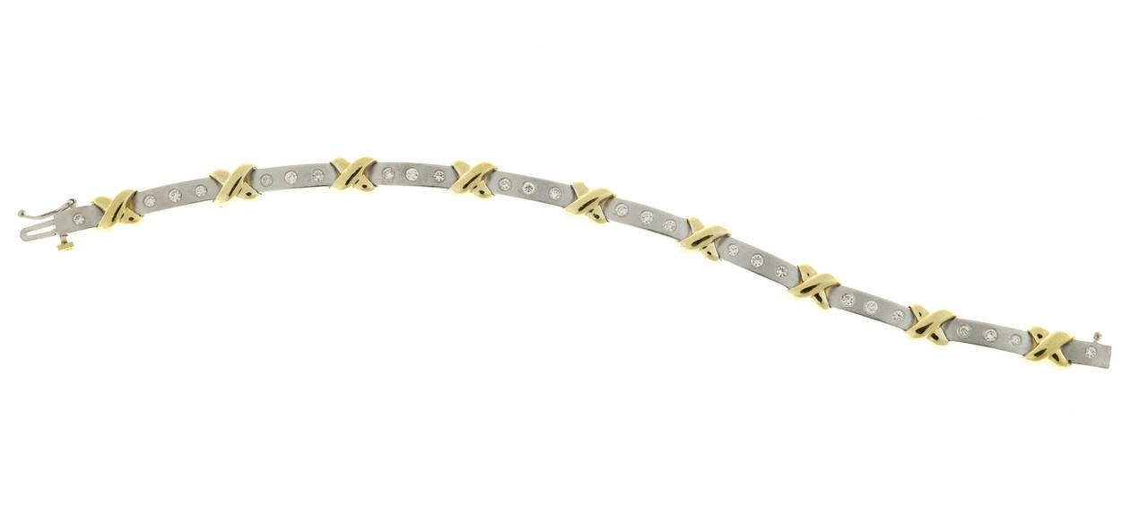 Beautiful solid 18k yellow and white gold hinged link bracelet.  White gold textured bar links set with bright white full cut diamonds.  The links are connected by 18k yellow designs.  Hidden box catch and side safety.