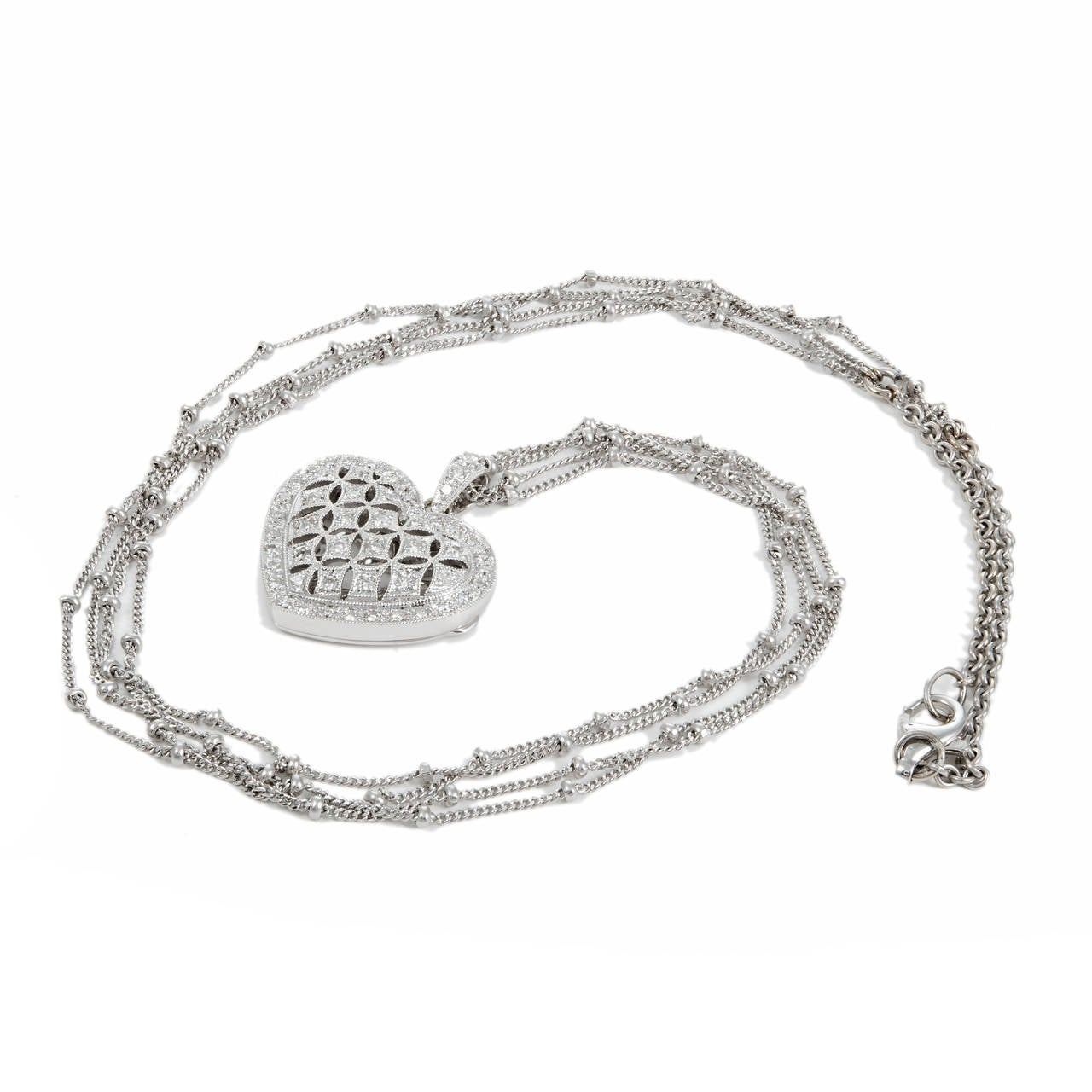 Beautiful 18k white gold open work diamond heart pendant. Hinged back opens. Inner frame to hold a picture  52 full cut diamonds, approx. total weight .50cts, G, VS to SI 20.5 inch chain stamped and tested 18k with 17.5 inch double bead chain and