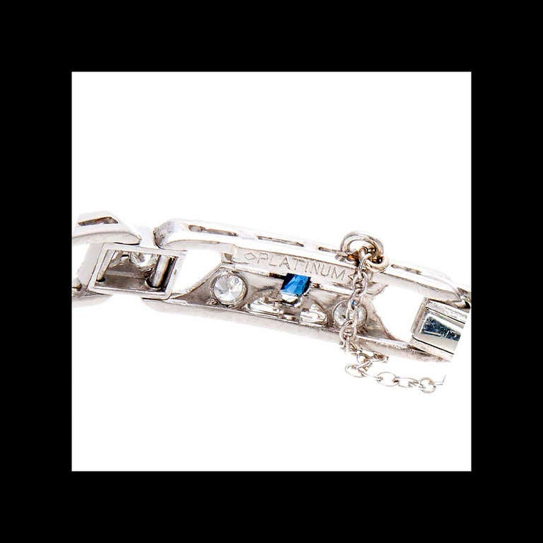 Late Art Deco hinged link bracelet circa 1930-1940 set with fine bright blue Calibre or Swiss cut Sapphires and bright sparkly diamonds. Platinum bracelet and sparkly chain. White gold spring ring.  Platinum  9 genuine bright blue Calibre or Swiss