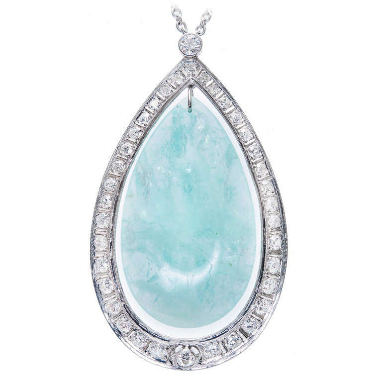 1940's natural pear shaped 75.00ct Aquamarine pendant in a Platinum diamond halo frame with chain.   Platinum 1 light slightly greenish blue Aqua pear double cabochon, approx. total weight 75.00cts, natural minor inclusions, totally natural and