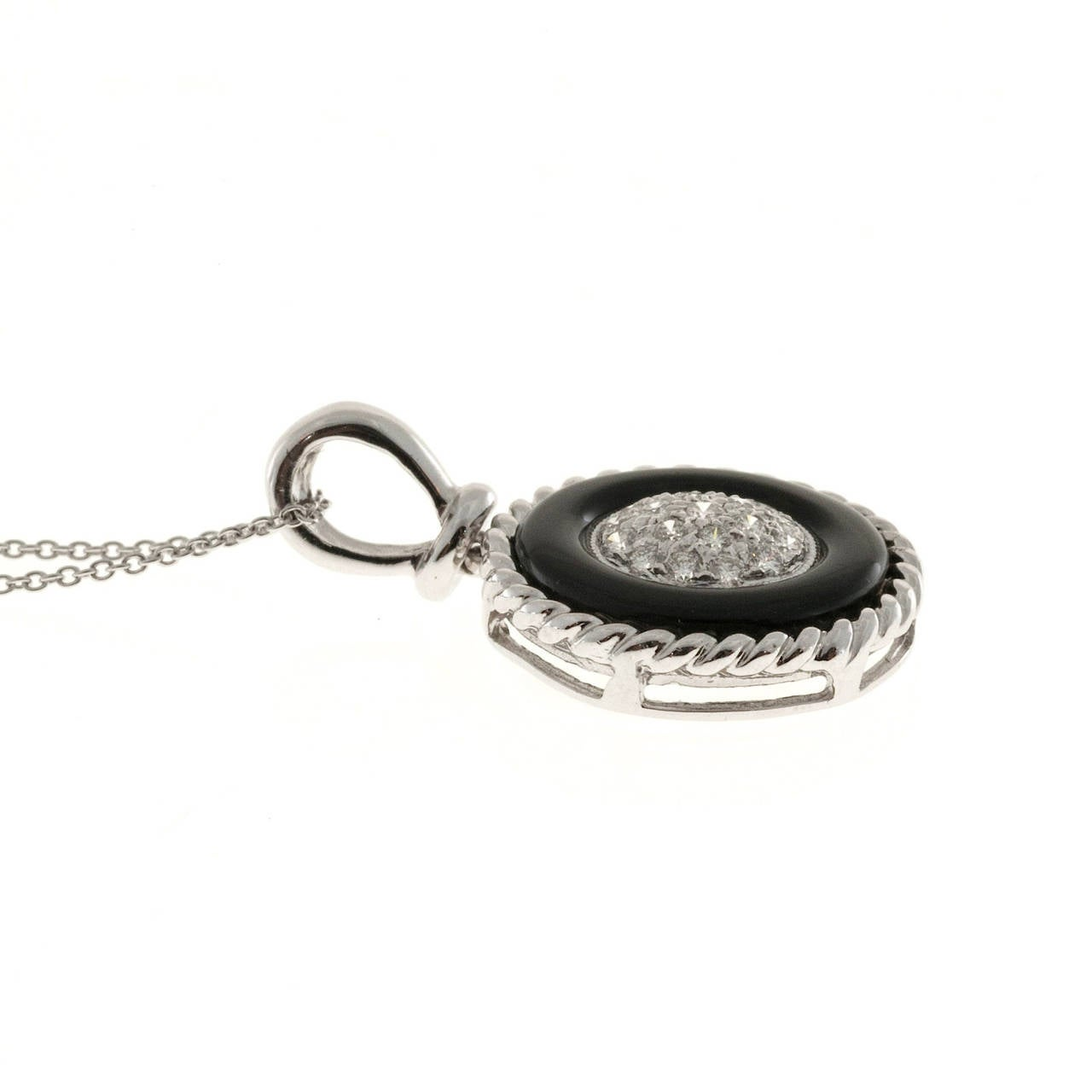 Estate solid Platinum rope border pendant with a genuine black onyx circle. The center is slightly domes and pave set with good diamonds. Chain is solid Platinum as well. Unique item in excellent condition.