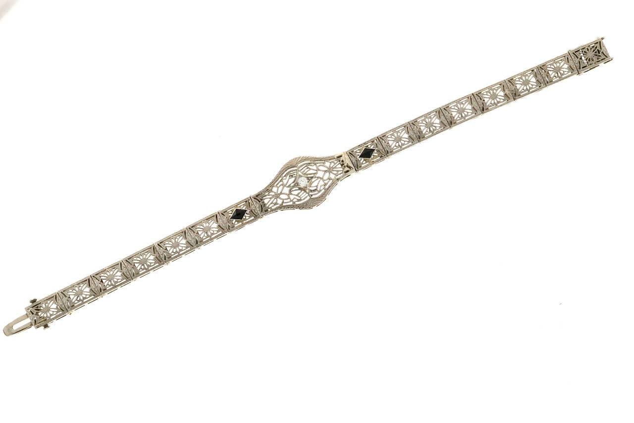 Art Deco filigree hinged link bracelet set with a nice European cut diamond and two deep blue calibre cut Sapphires. Circa 1940.  2 Marquise shaped calibre cut Sapphires 4.5 x 2.5mm 1 European cut diamond, approx. total weight .05ct, G, SI1 14k