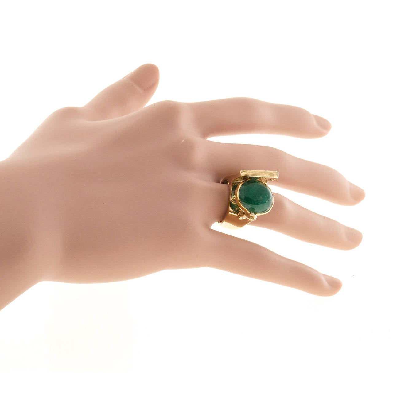 Extremely unusual one of a kind 1950's designer ring, signed Jordin.  Very heavy solid construction bezel set with a natural very good color deep green emerald. Side signed: Jordin. Translucent emerald. Textured and shiny finish. Well-polished