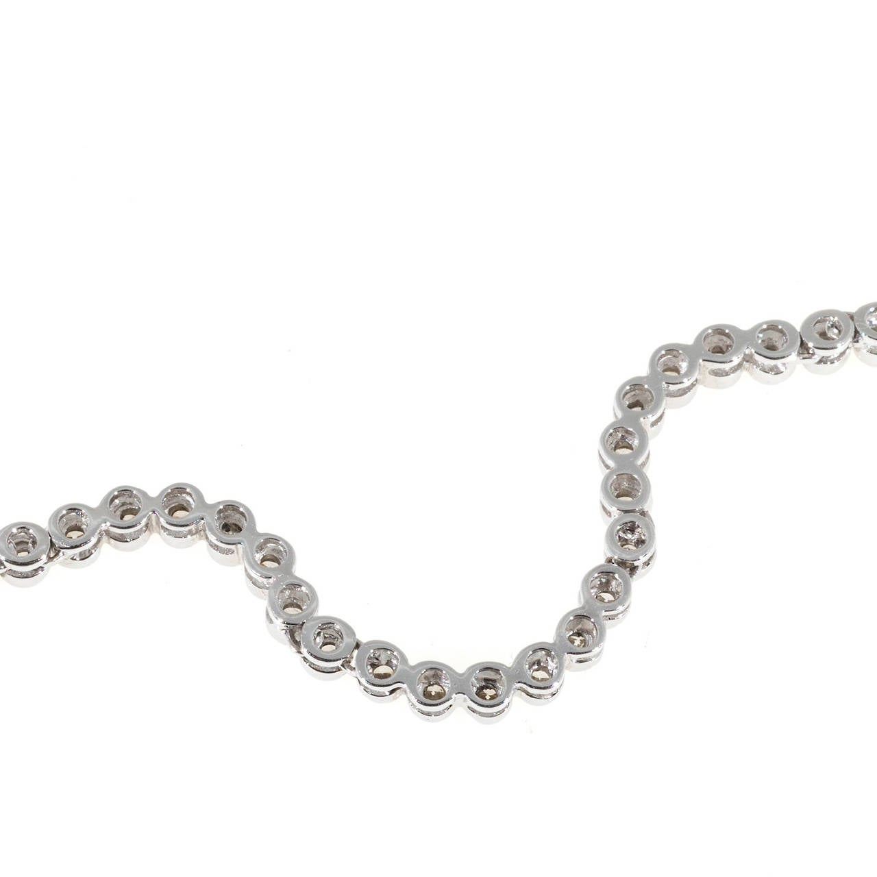 Wonderful simple but different swirl link tube set 18k white gold diamond necklace with hinged links and sparkly white full cut tube set diamonds. Built in catch and figure 8 safety. Circa 1980.