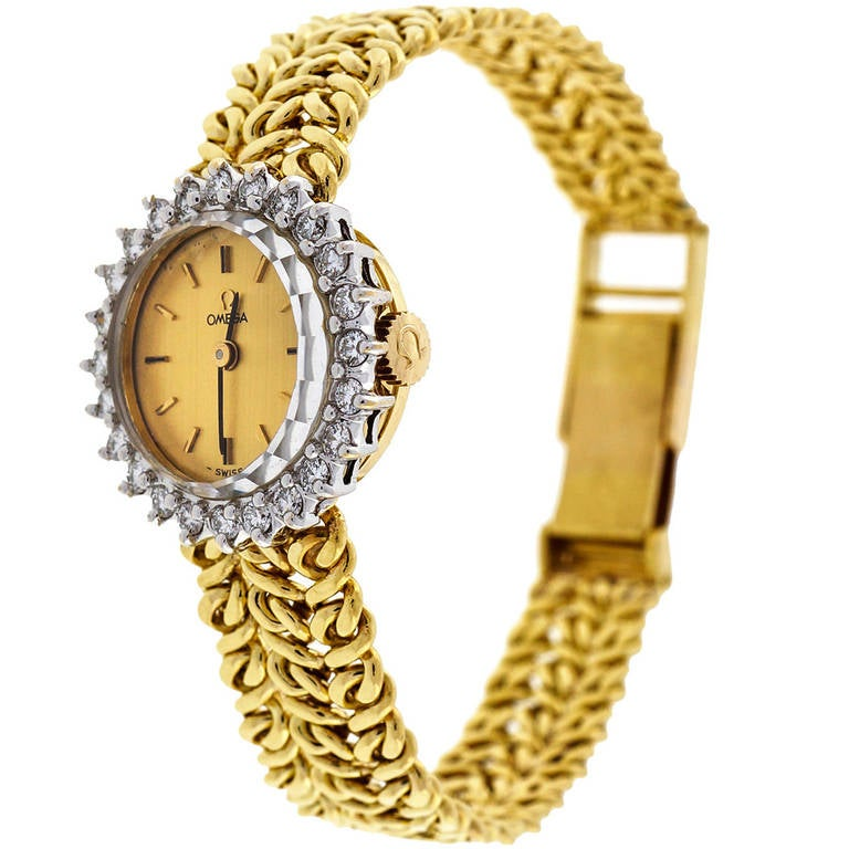 Omega lady's 18k yellow gold and diamond bracelet wristwatch. Omega manual-wind movement.  24 full cut diamonds 0.75cts total G, VS2 18k yellow gold Bracelet Length: 6 1/4 to 6 3/4 inches, clasp is adjustable Width: 21mm Bracelet width at case: