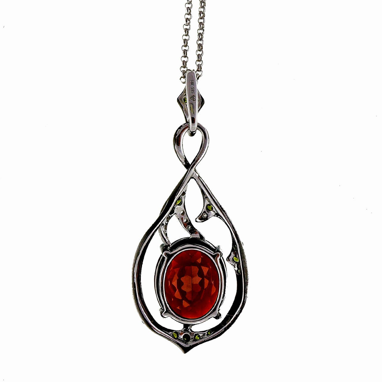Beautiful blackened white gold swirl pendant with bright red oval Garnet and white and irradiated green diamonds. Circa 1980.  1 oval red Garnet, approx. total weight 5.00cts, SI, 12 x 10mm 15 irradiated light green single cut diamonds, approx.