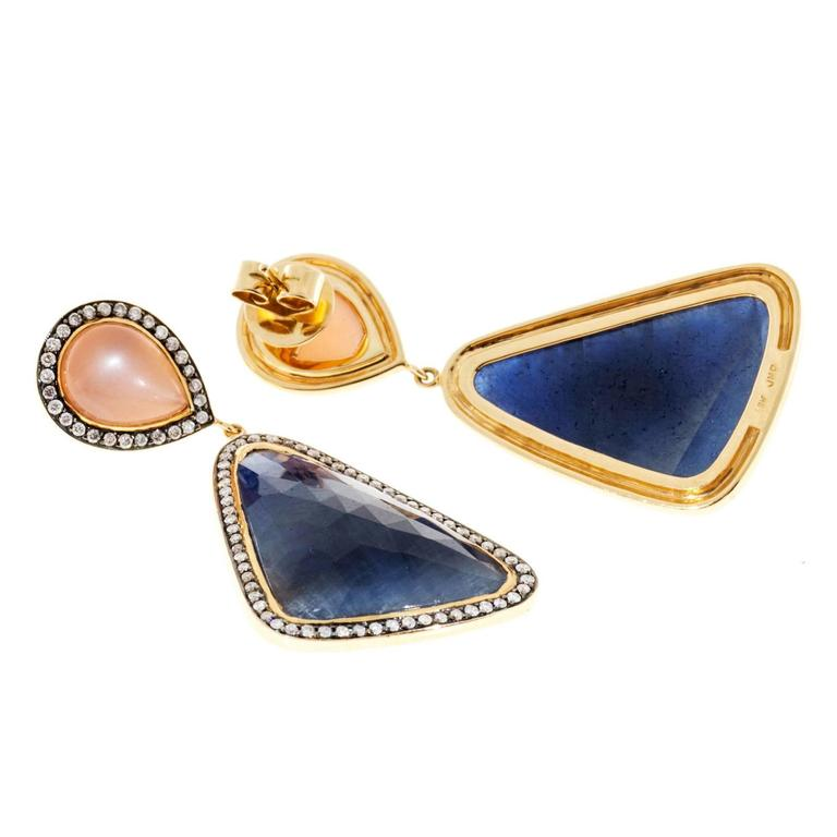 Designer 18k yellow gold dangle earrings with peach Moonstones and rose cut Sapphire slices from the designer JMP, surrounded by full cut diamonds. 