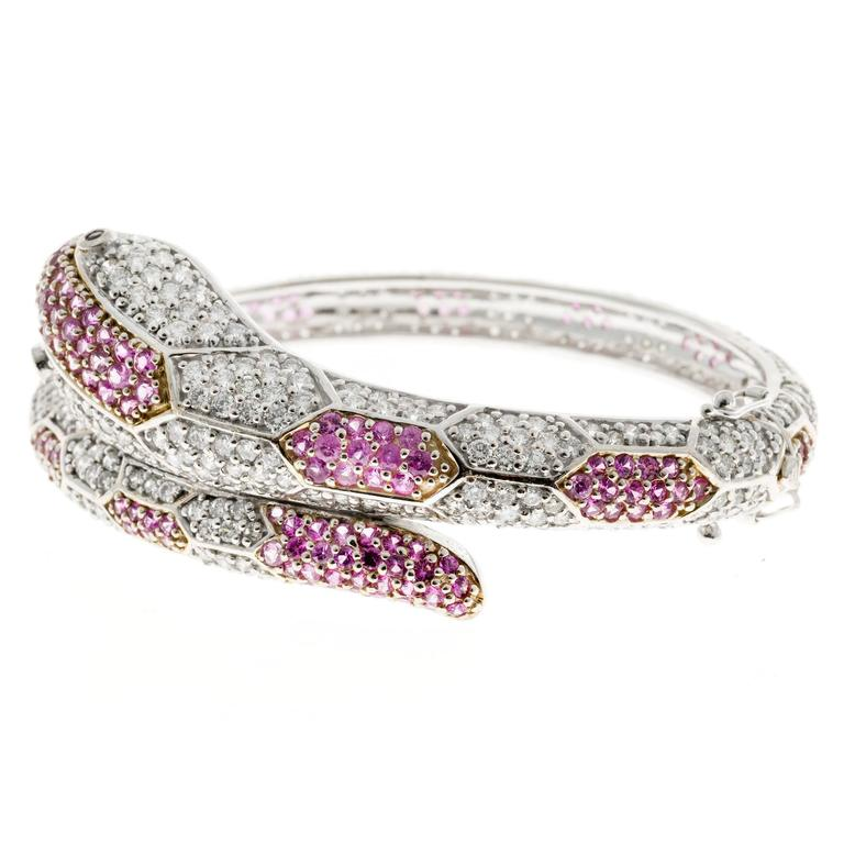 Ruby, diamond and sapphire snake hinged bangle bracelet in 18k white gold. Bright white full cut diamonds, Ruby eyes and bright pink Sapphires. Hidden catch and double figure 8 safety.   316 full cut round diamonds, approx. total weight 8.00cts, H,