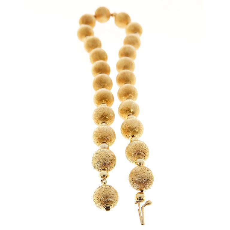 Textured and shiny heavy 18k yellow gold 18 1/2 inch bead necklace. Built in catch. Nice heavy secure chain as well. The texture of the large beads gives a rich warm color.  Length: 18 1/2 inches Heavy thick walled beads, secure catch and chain,