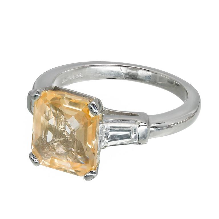 Three stone Natural orange yellow Emerald step cut Sapphire engagement ring. GIA certified in its original handmade Platinum setting with full size tapered baguette diamonds. Circa 1930-1940.  1 octagonal step cut orangey yellow Sapphire, approx.