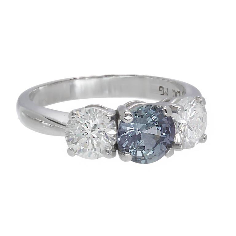 Peter Suchy GIA certified natural no heat color change Sapphire engagement ring. Sapphire changes color in different lights from grey blue to grey purple. Also, set with 2 round brilliant cut Diamonds in a three-stone platinum setting  1 round color