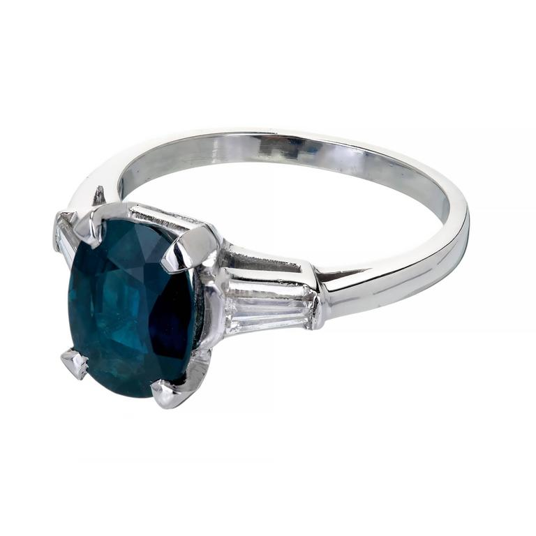 Vintage 1950 three-stone Platinum engagement ring with a deep blue 3.01ct GIA certified natural no heat oval Sapphire and tapered baguette Diamond accents.  1 oval blue Sapphire, approx. total weight 3.01cts, MI, natural no heat, 9.63 x 7.32 x