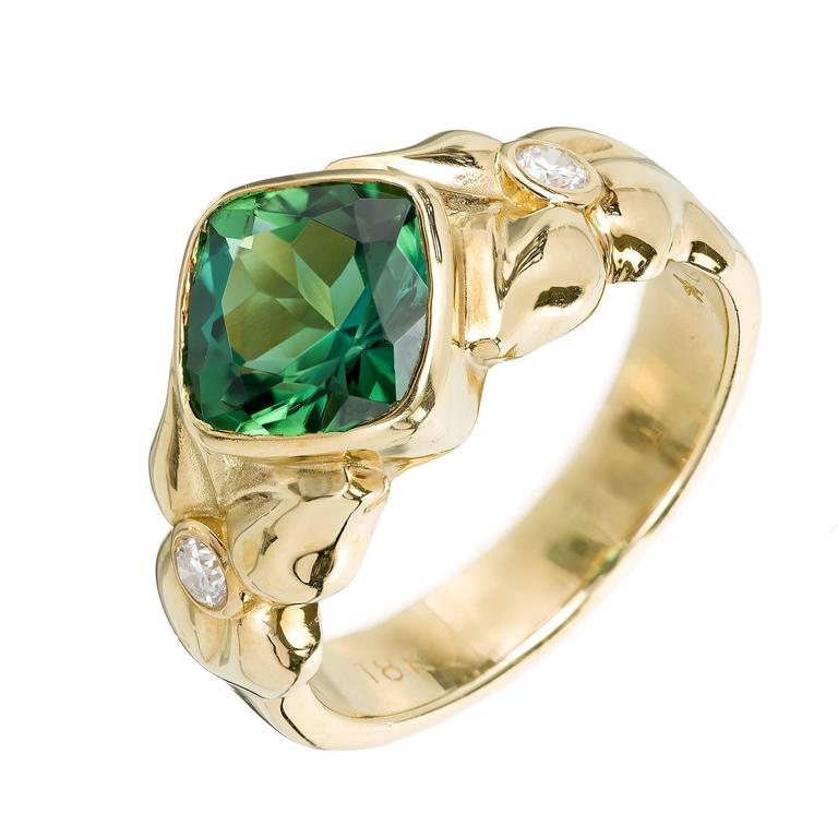 Fine gem green cushion cut Tourmaline ring in a handmade 18k yellow gold flower motif bezel setting, with two accent diamonds  1 cushion green Tourmaline, approx. total weight 2.50cts, VS 2 round Diamonds, approx. total weight .06cts, G, VS 18k