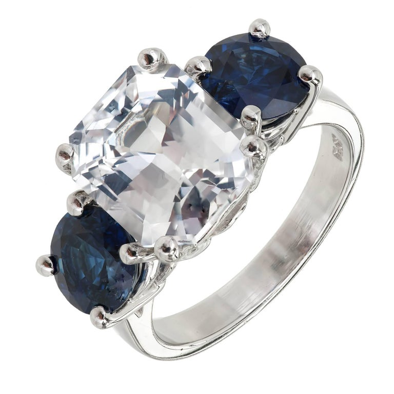 Octagonal step cut three-stone Sapphire engagement ring. Natural color no heat no enhancements and GIA certified center stone. Very light blue with good brilliance. Fine bright blue side Sapphires with excellent brilliance 2.80cts total. In a custom