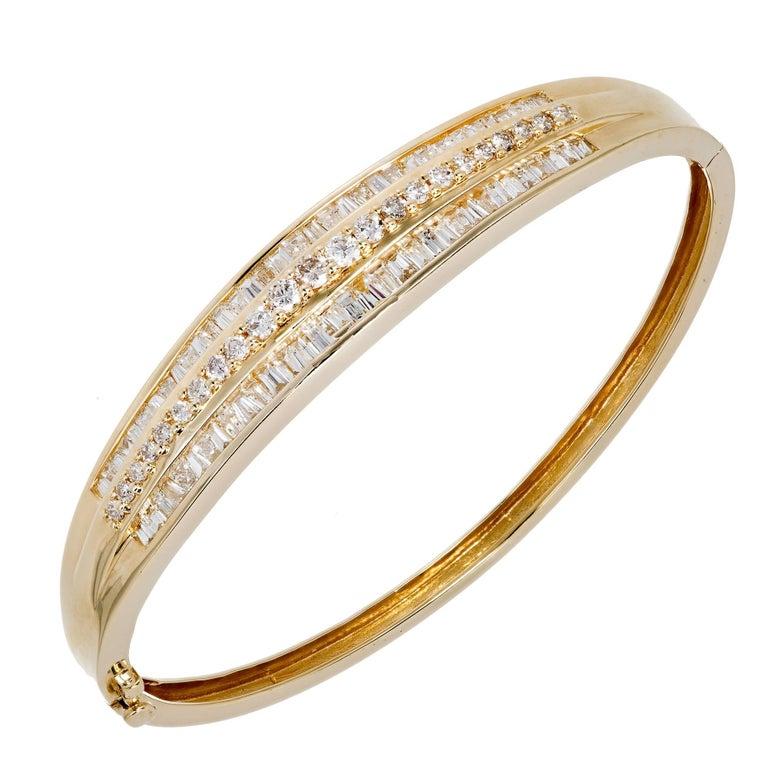 Fine diamond 3 row baguette and round diamond hinged 14 karat bangle bracelet. Underside safety.   66 baguette cut diamonds, approx. total weight 1.20cts, H, VS-SI 23 round diamonds, approx. total weight .46cts, H, VS 14k Yellow gold 18.6