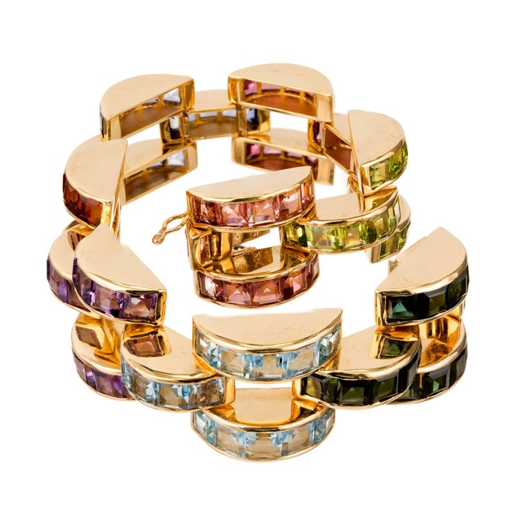 Domed channel set link bracelet with 8 different sets of colored stones of semi-precious varieties all presumed simple heat treated or irradiated, set in 14k yellow gold.   15 green step cut Tourmaline, approx. total weight 4.00cts, VS, 4.2 x