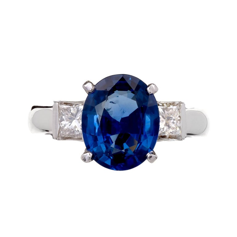 Bright blue oval Sapphire 3.04ct three-stone engagement ring with Princess cut side Diamonds in a 14k white gold setting. GIA certified natural Sapphire simple heat only.   1 oval bright blue Sapphire, approx. total weight 3.04cts, SI1, 3.53 x