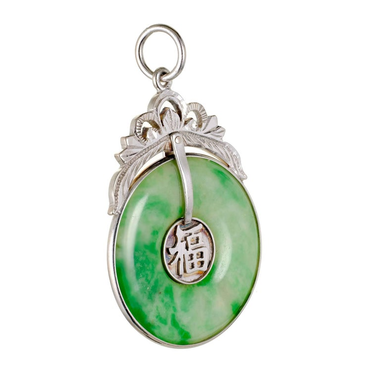 Round natural bright mottled green Jadeite Jade Hololith pendant with a 14k white gold frame and top. Hand engraved and GIA certified.  1 Hololith mottled green Jadeite Jade, 25.77 x 25.73 x 2.73mm, GIA certificate #2181636976 14k white gold Top to