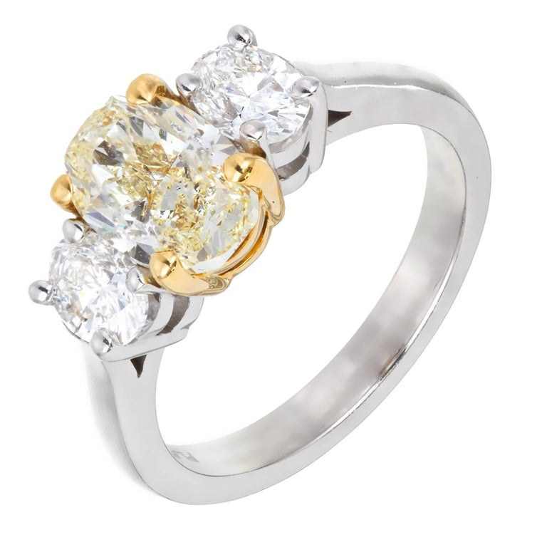 Three-stone oval yellow diamond 18k white gold engagement ring. A handmade setting from the Peter Suchy Workshop is set with 3 incredibly bright sparkly oval diamonds. The side stones are E-F color, VS2. The center oval is fancy light yellow set in