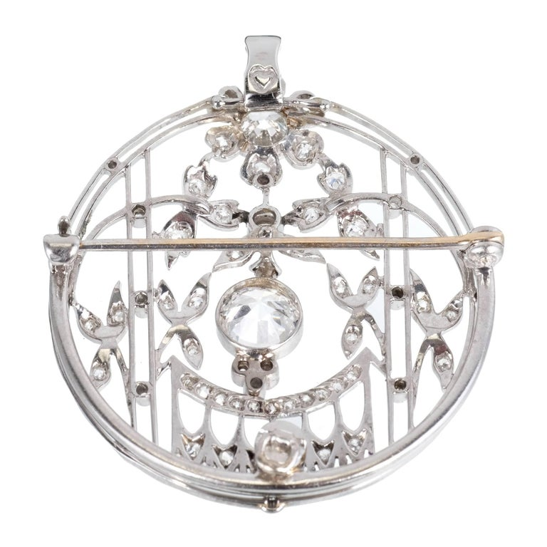 1930s Art Deco Edwardian style pin pendant diamond circular design. Center diamond is flexible and EGL certified 1.21ct E, SI2 European cut. Bright and sparkly Platinum bail flips up to make a pendant. A screw in fitting can be removed to take off