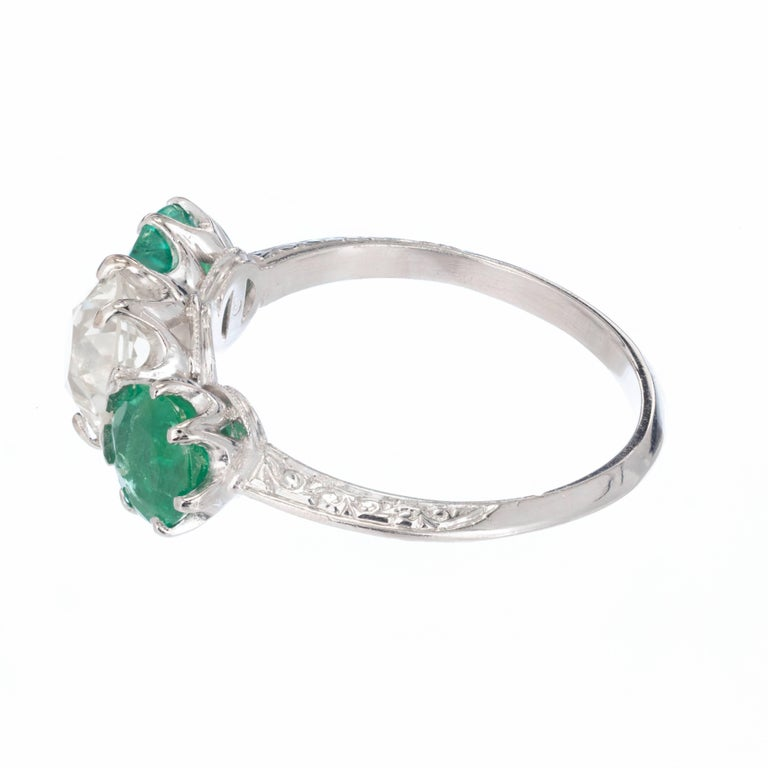 Art Deco diamond and emerald engagement ring. delicate engraving and pierced work. Old European cut round diamond extremely bright and well cut, with two bright green emeralds on each side. Moderately clear and moderately included. The color of the