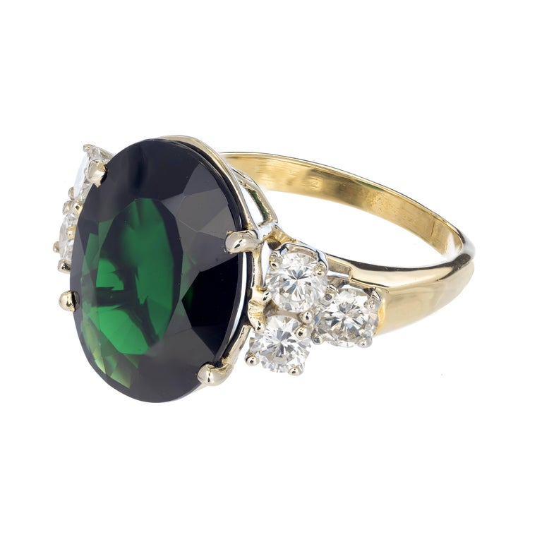 Deep large oval green Tourmaline and diamond cocktail ring. Handmade 18k yellow and white gold setting with 3 bright sparkly brilliant cut diamonds on each side help set off the rich emerald green color of this genuine Tourmaline.   1 Natural green