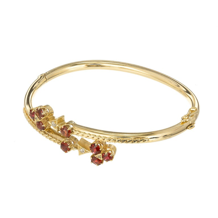 14k Yellow gold diamond and garnet bypass bangle. Three round garnets prong set with a diamond in the center attached to a triangular setting with a round diamond makes a clover like design attached to an additional garnet.   8 old European cut