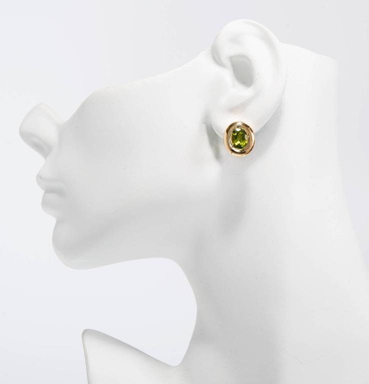 Women's 4.10 Carat Oval Green Peridot Domed Gold Bezel Stud Earrings For Sale