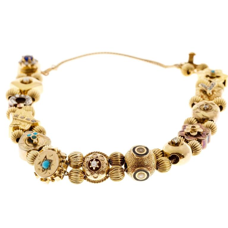 1930's Original 14k yellow gold slide bracelet. From the female side: 4mm genuine old cut sapphire with 6 pearls, 2mm natural pearls, horseshoe with rose cut diamonds, shield with small natural pearls, heart with 3 turquoise, circle with 2.5mm