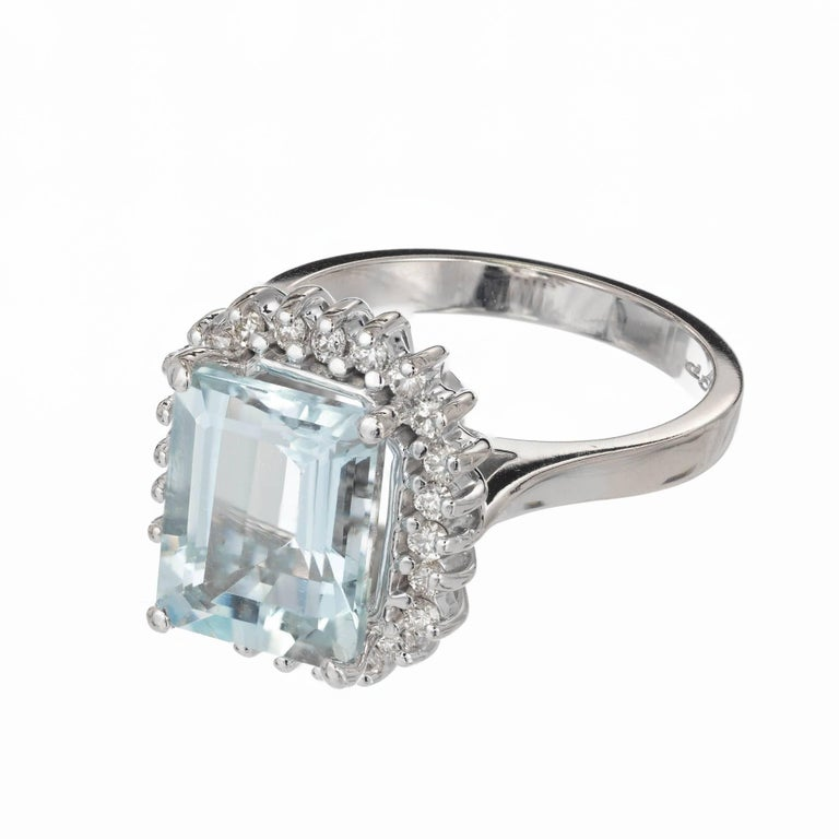 Bright natural untreated slightly greenish blue natural Aqua and diamond halo cocktail ring. In a 14k white gold setting surrounded by a halo of diamonds.  1 Emerald cut bright greenish blue Aqua, approx. total weight 3.00cts, VS, 10.2 x 8.2mm 24