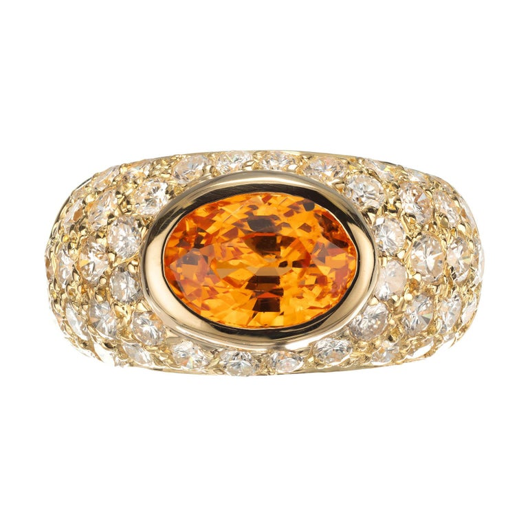 Spessartite Garnet and diamond dome cocktail ring. The oval Spessartite center stone is set sideways in a handmade dome 18k yellow gold setting with round pave diamonds.   1 oval bright orange Spessartite Garnet, approx. total weight 2.43cts, VS 45