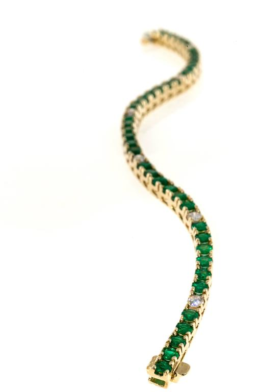 Green Emeralds and full cut diamonds in a 14k yellow gold hinged link bracelet with built in catch and underside safety.