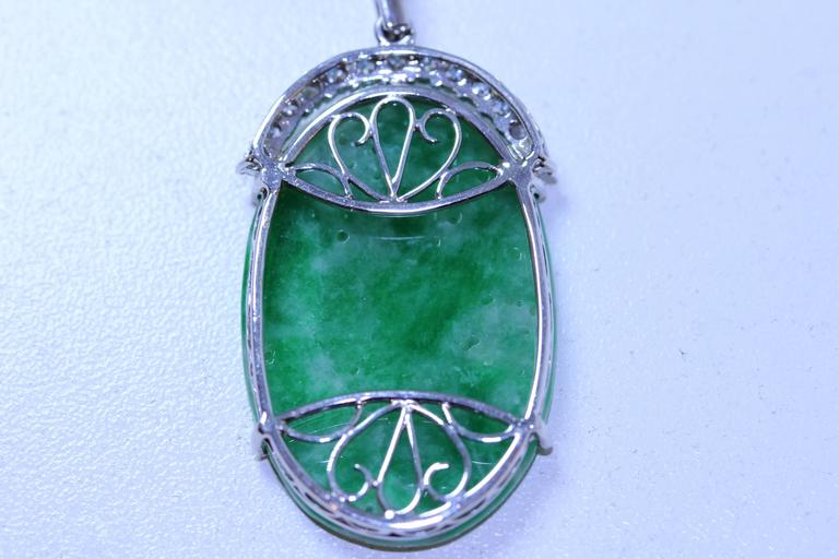 18 karat white gold carved pierced jadeite butterfly, lotus flower with diamonds. Diamonds equal .70 total weight. 16 inch diamonds by the yard chain. 9 diamonds equal .05 total weight. I-J in color. GIA report.