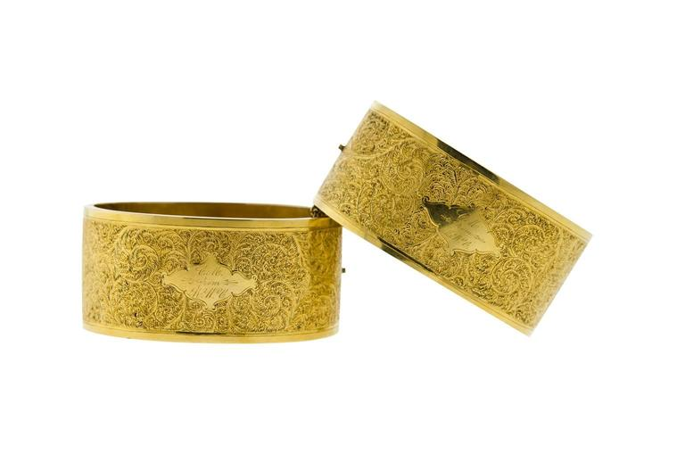 "Beautiful pair of Victorian 14 karat yellow gold stiff hinged bangle cuff bracelets. Measuring 1 1/8"" wide. Very fine detailed engraving on both sides. No denting. One bracelet has small rub mark on the rim. Each bracelet has one gold safety chain."