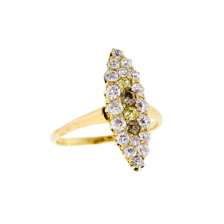 This sweet antique turn-of-the-Century yellow gold and diamond ring, within a navette shaped setting, is set with two stunning Old Mine Cut yellow diamonds weighing approximately 0.12cts total and 18 dazzling Old European Cut and Old Mine Cut