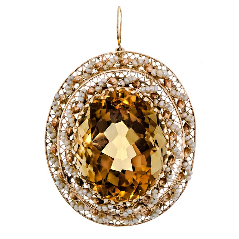 Dramatic citrine and seed pearl pendant/brooch containing one oval shape mixed cut citrine measuring approximately 27.00 x 21.00 x 15.50 mm. Accented with numerous round seed pearls and handcrafted 14k yellow good. A quality mark is stamped on the
