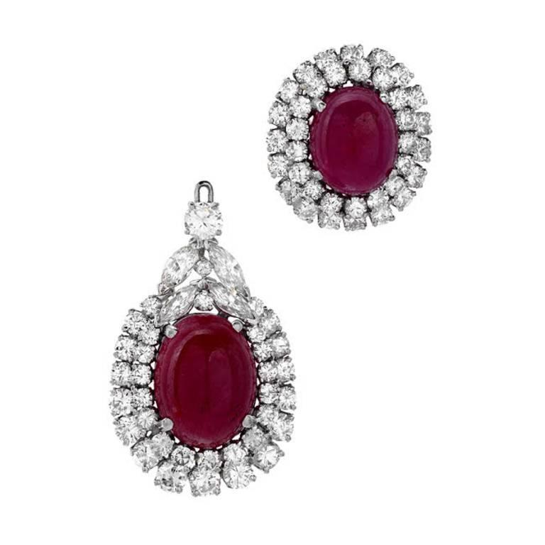 This extravagantly bold pair of earrings are not for the faint of heart! 46.30 carats of deep red cabochon rubies take center stage in these detachable drop earrings. The 18.80 carats of round and marquise cut white VS quality diamonds hold their
