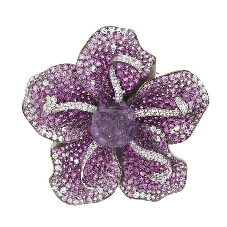 This unique piece can be worn three ways, as a ring, pendant and brooch. The ring shank slides on and off the bottom to easily change from ring to brooch and back. It features 4.06 carats of diamond, 16.17 carats of pink and purple sapphire, and a