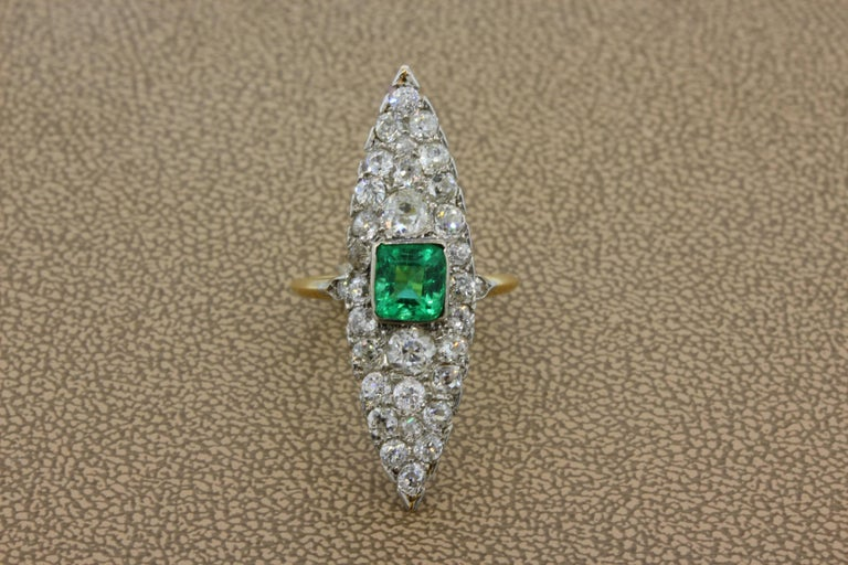 A classic Navette ring from the early 1900's featuring a 1 carat emerald cut emerald. There are 1.94 carats of old-cut diamond accents around the luscious emerald, set in 18K yellow and white gold.   Navette Length: 1.48 inches   Size: 6