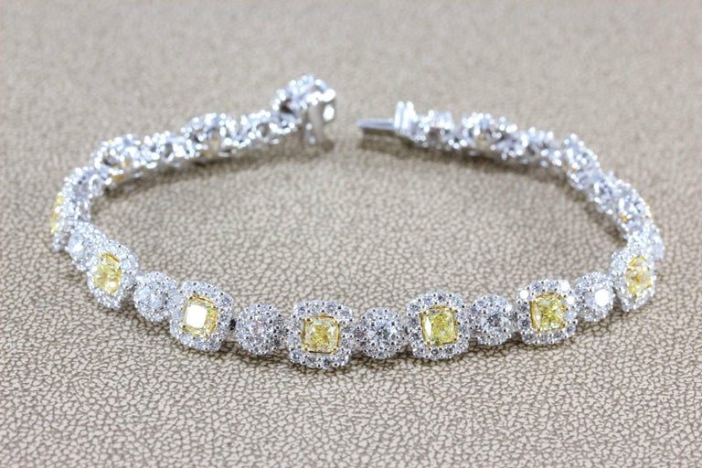 A sleek and sexy tennis bracelet featuring 5.68 carats of fancy yellow cushion cut diamonds, which are enhanced by 7.33 carats of VS quality white diamonds. All set in 18K white gold, the bracelet is blanketed in sparkling diamonds that dance in the