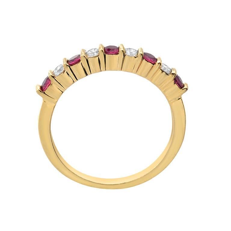 This ring features 5 round cut rubies weighing 0.40 carats and 4 brilliant cut diamonds, VS clarity and F-G color weighing 0.25 carats. Made in 18K yellow gold.  Ring Size 6 (Sizable)