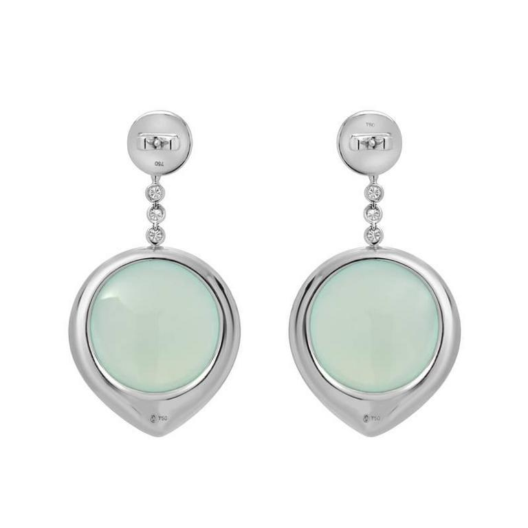 A pair of one-of-a-kind earrings featuring soft blue chalcedony which are haloed by 3.14 carats of lively blue and white diamonds. These elegant drop earrings are set in 18K white gold with flexibility and movement.  Earring Length: 2.10
