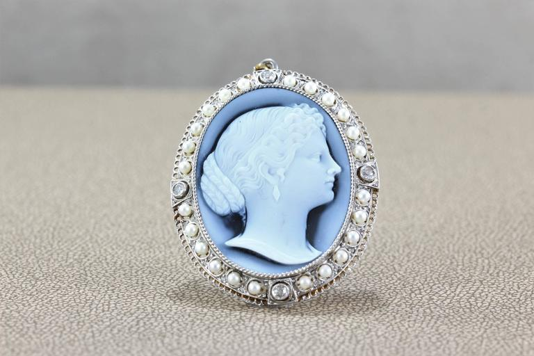 A fine quality hardstone cameo with sharp detail, accented by diamonds and seed pearls set in a 18K gold frame with scroll motifs and milgrain setting. The frame is topped with platinum.   Can be worn as a brooch or pendant, which do you