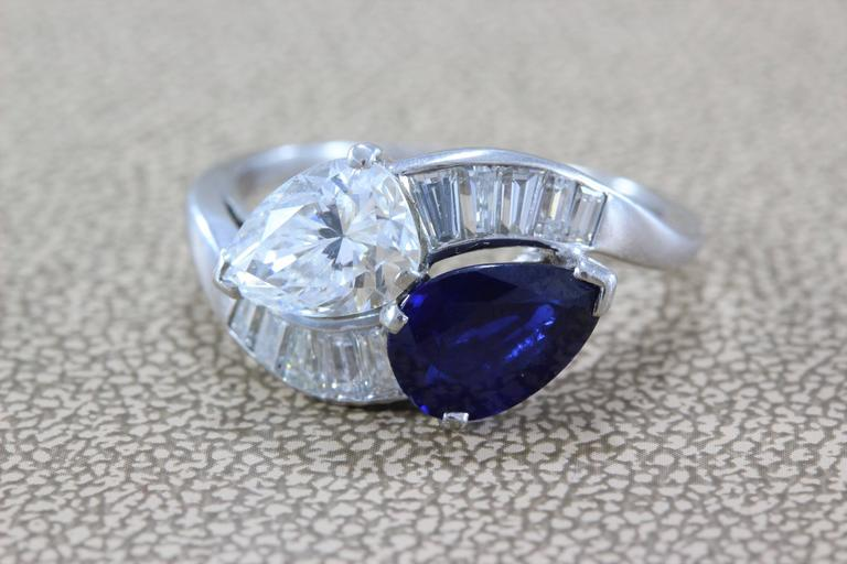 A stunning sleek bypass ring featuring a 1.27 carat GIA Certified pear shape diamond, F/SI1, and a 1.30 carat richly colored blue pear shape sapphire. Diamond baguettes accent the two stones, all set in platinum.   Two ways to wear the ring, diamond