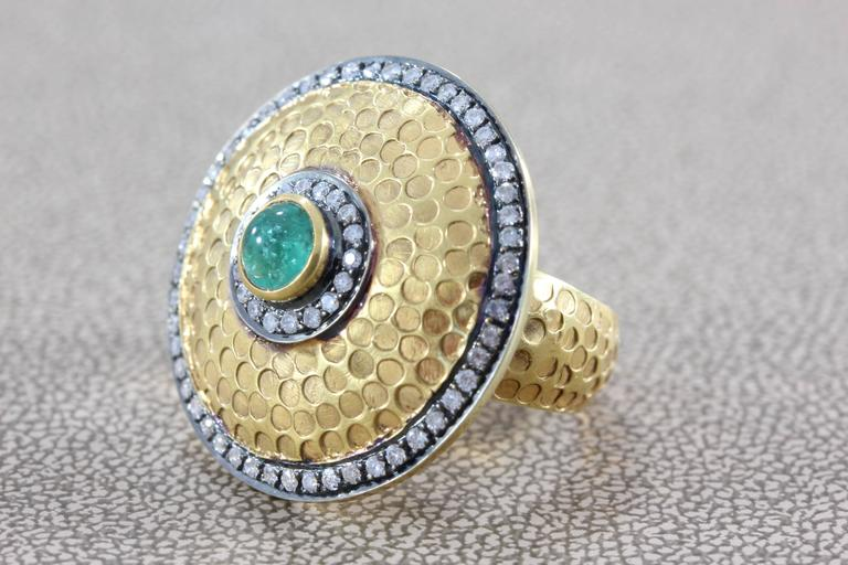 A unique design, this shield ring centers a 0.30 carat cabochon emerald, bezel set. Accenting the piece are about 0.65 carats of diamonds all set in 14k gold. A stylish look with a hammered gold finish.  Dimensions: 1.0 x 1.0 inch  Ring size 6.50