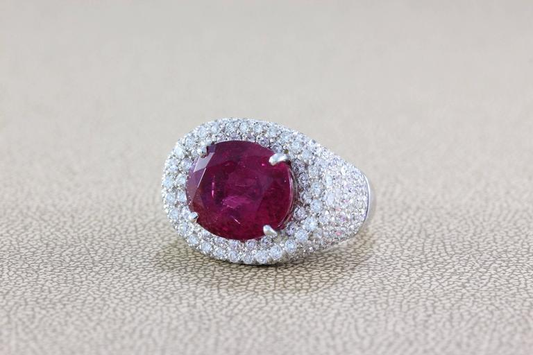 A ring featuring a superb gem rubellite tourmaline weighing in at 12.16 carats. This gem displays a magnificent vivid raspberry red color that rivals the finest of rubies. Accenting the gemstone are over 4 carats of full-cut diamonds, all set in 18K