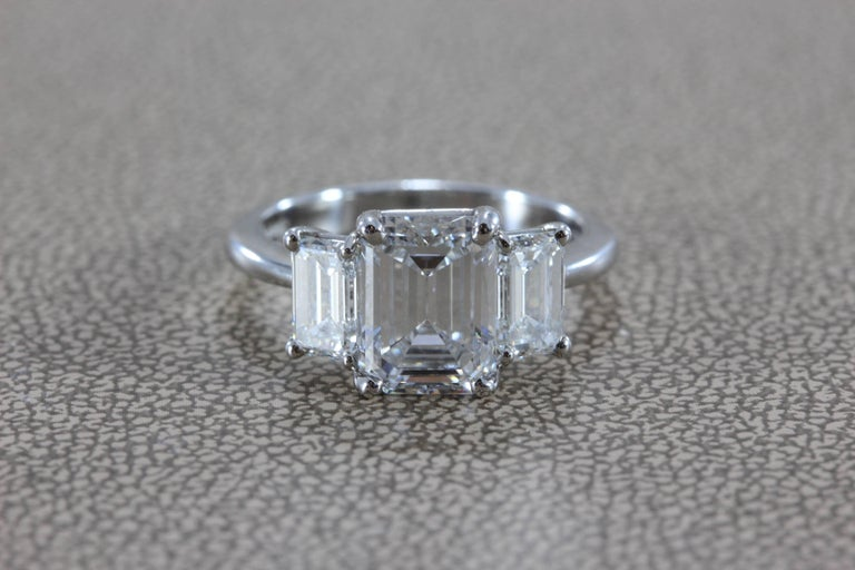 This luxurious engagement ring features a top quality 2.28 emerald cut diamond with E color and VVS2 clarity. The diamond is beautifully cut with excellent proportions and no florescence, a true top-grade gem of a diamond. There are two smaller