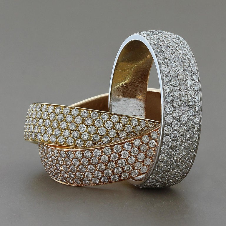 As good as it gets, the three interlocking Rose White and Yellow Gold bands are covered with 6.78 carats of VS quality round cut diamonds. The craftsmanship and finish are second to none, a true piece of fine jewelry.   Size 7